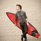 Flutist Garrett Hudson of WindSync poses with a surfboard | Houston, USA